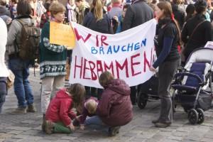 """Zwei Frauen halten ein Transparent mit der Aufschrift """"Wir brauchen Hebammen"""""""