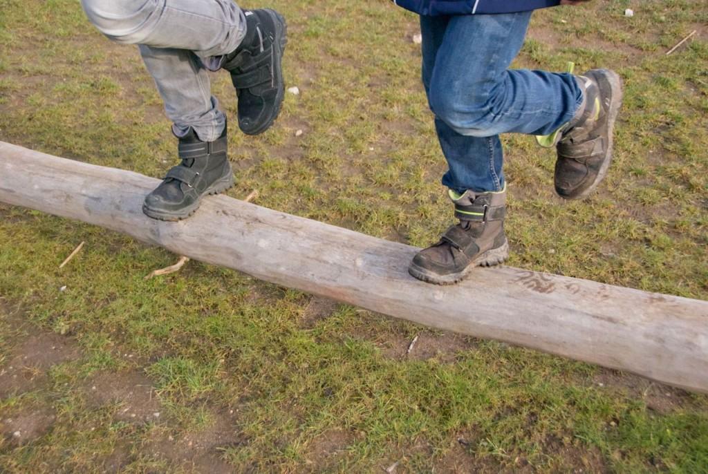 Balanzierbaumstamm und die Beine von zwei Kindern, die auf einem Bein stehen