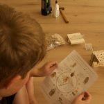 Lesen der Anleitung, im Hintergrund: Bauteile und Werkzeug