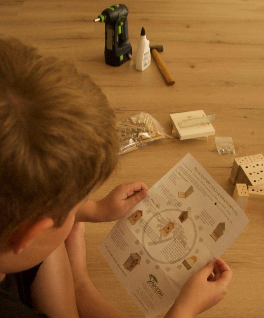 Lesen der Anleitung zum Zusammenbau des Insektenhotels, im Hintergrund: Werkzeug und Bauteile