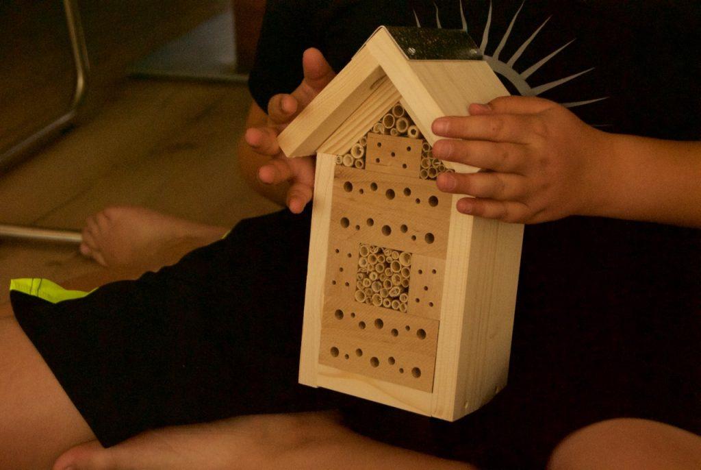 Kinderhände halten fertiges Insektenhotel